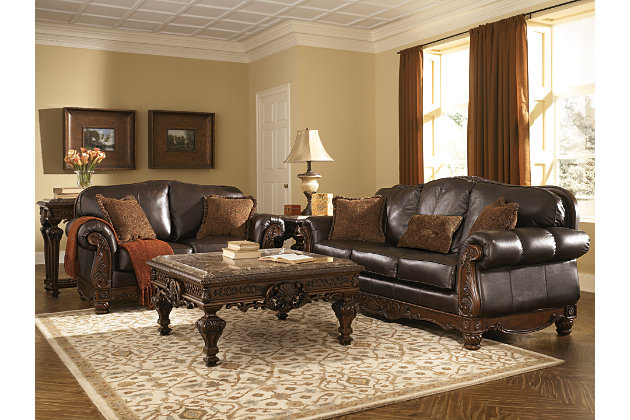 dark brown leather couch and leather loveseat with intricate wood details