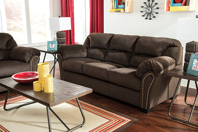 Nailhead Trim Outlines the Curved Frame of this Dark Brown Couch and Loveseat