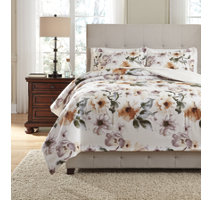 water colored floral patterned white comforter set with a white shag rug